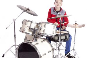 Teenager plays drums in studio with white background